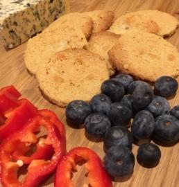sprø ostekjeks på fat med blåbær og paprika